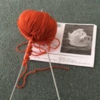 Knitting needles and orange yarn